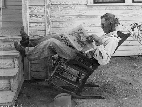"""Farmer reading his farm paper"" By George W. Ackerman, Coryell County, Texas, September 1931, from Wikipedia Commons"